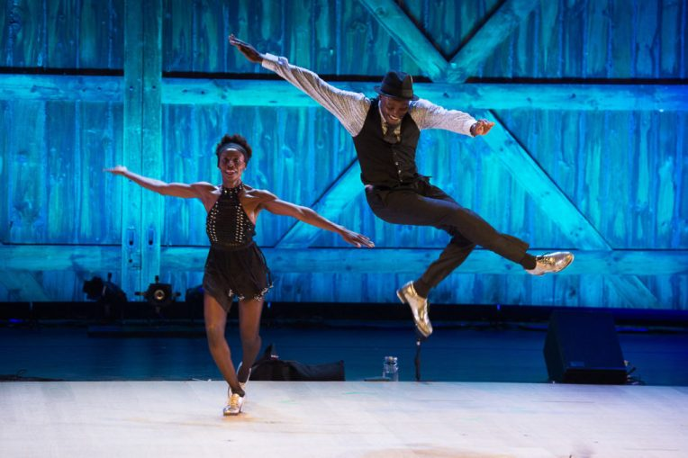 Two tap dancers on stage, blue light background